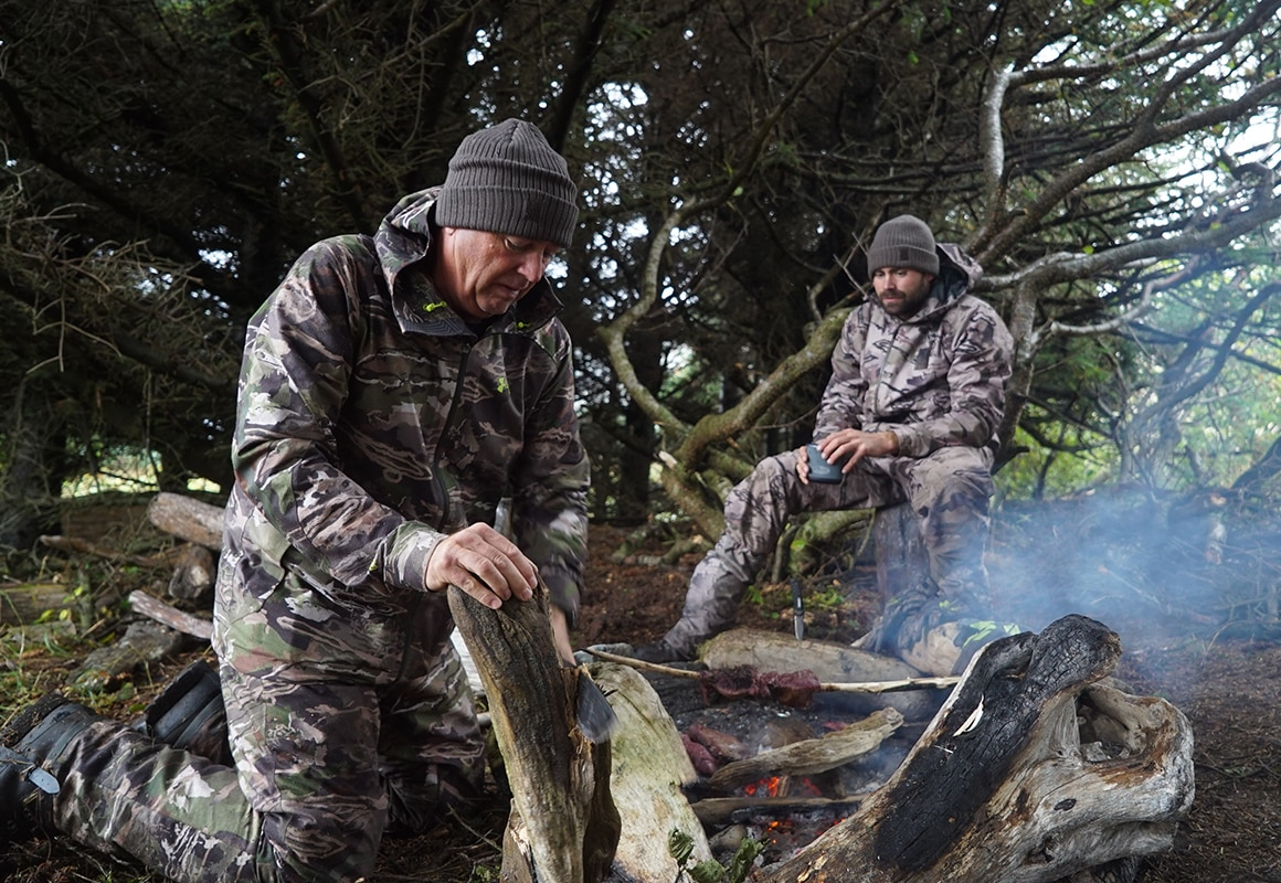 onX pro-staffer Remi Warren & son cooking sitka blacktail venison on a hot rock camp fire.