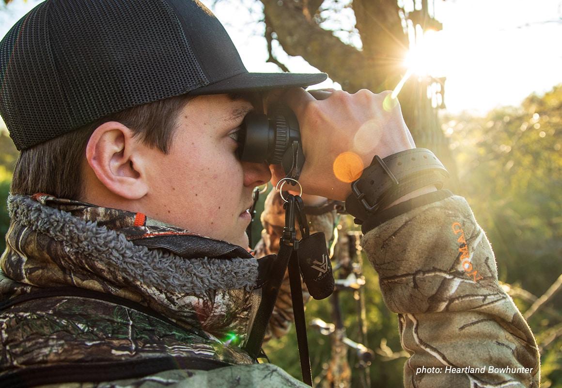 Man looking through binoculars while hunting whitetail deer.