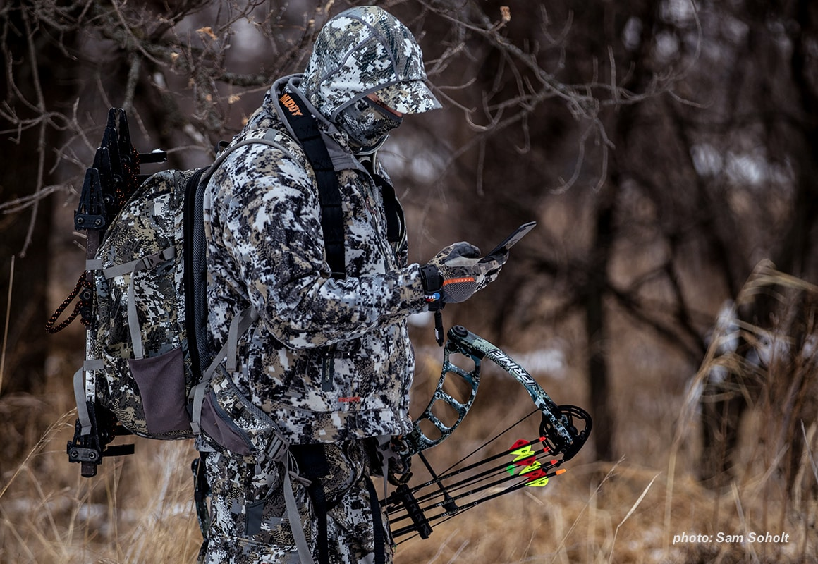 A man in full camouflage and a compound bow checks his onX Hunt App on his mobile phone while hunting.