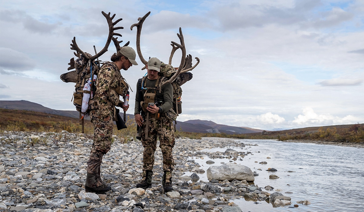 Two hunters pack out caribou after a successful hunt in Alaska.