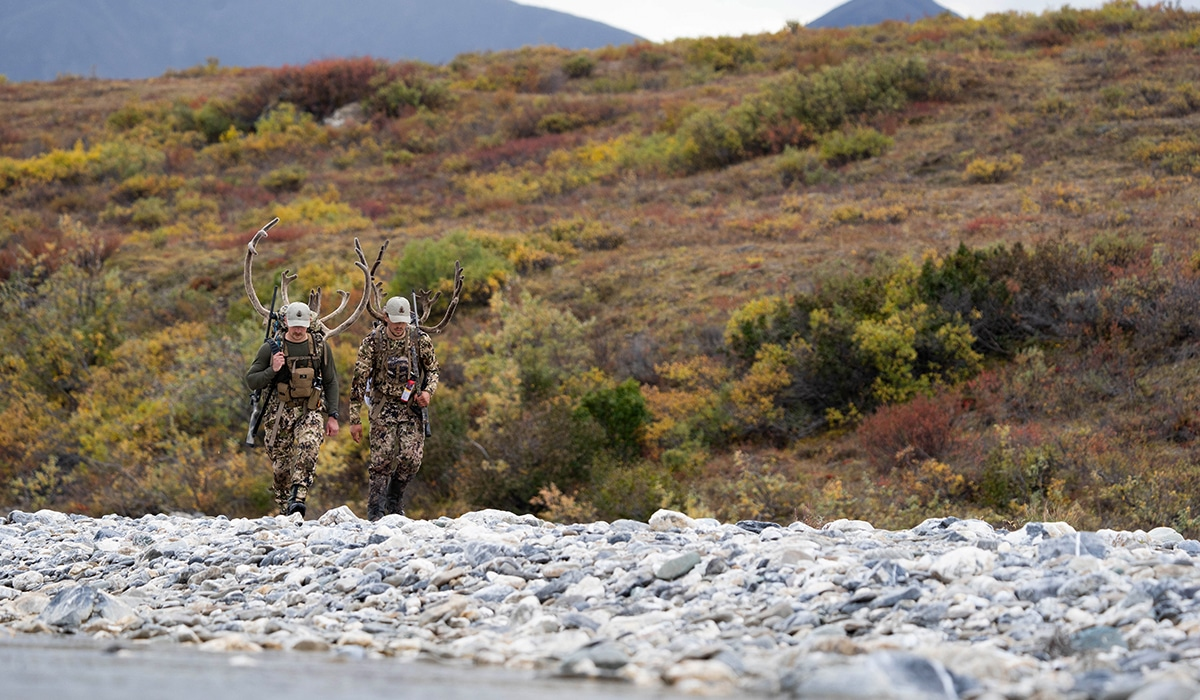 Two hunters carry out caribou meat after a successful hunt in Alaska.