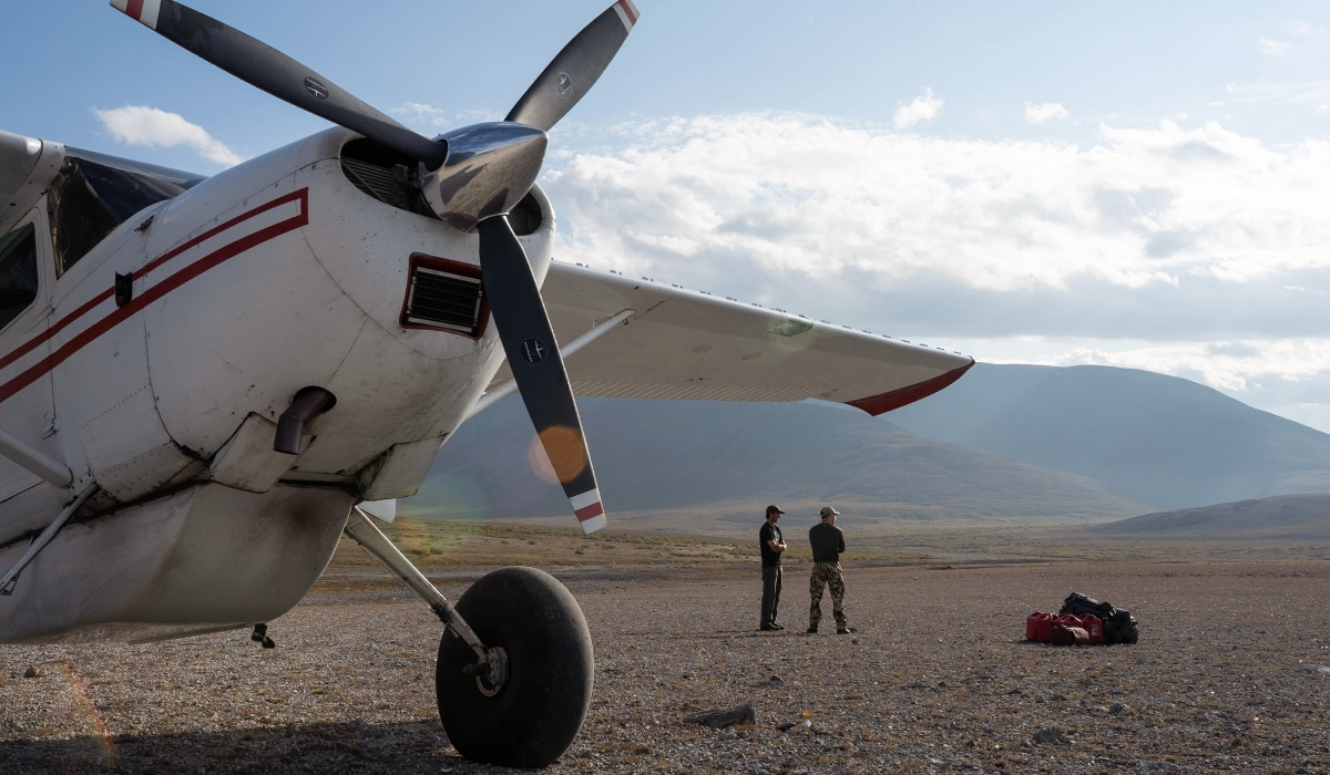 Arrival to the hunting site in Alaska, on a gravel bar with a bush plane in foreground.
