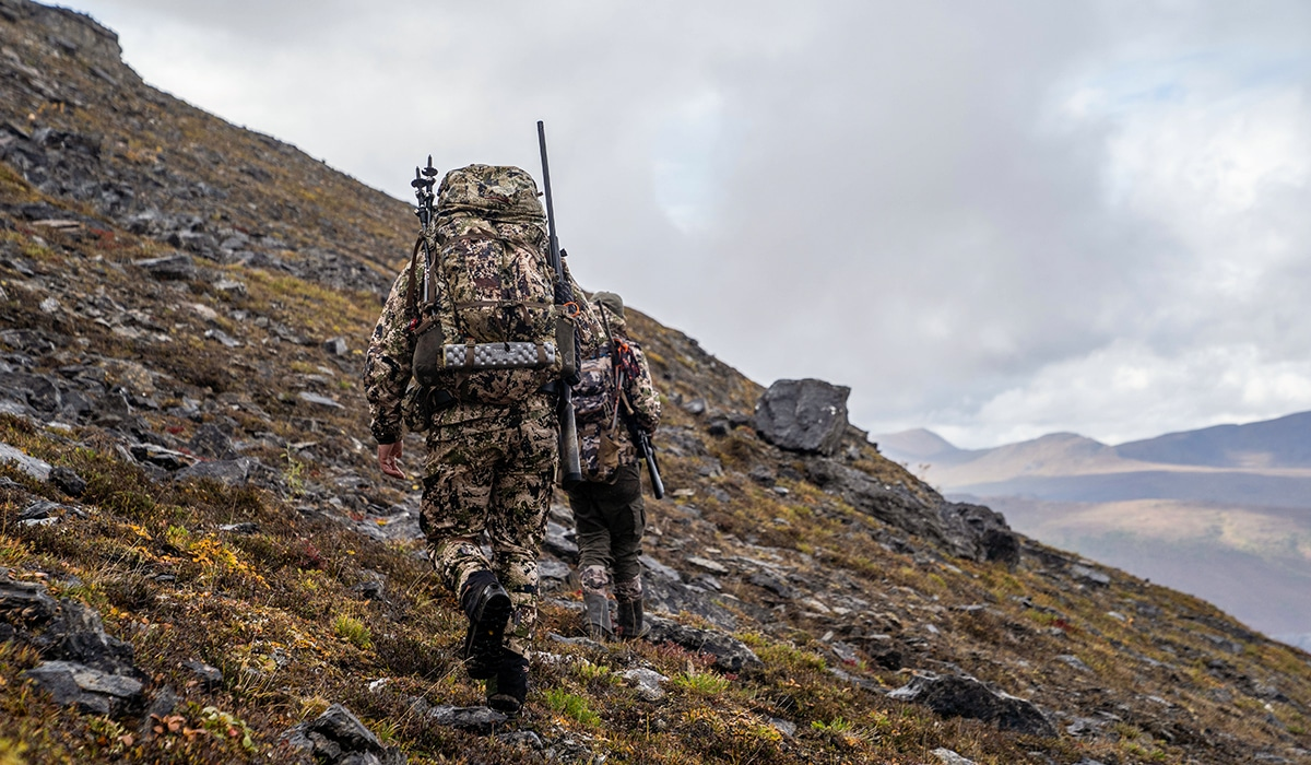 Two hunters hiking across mountains in Alaska as they hunt for caribou.