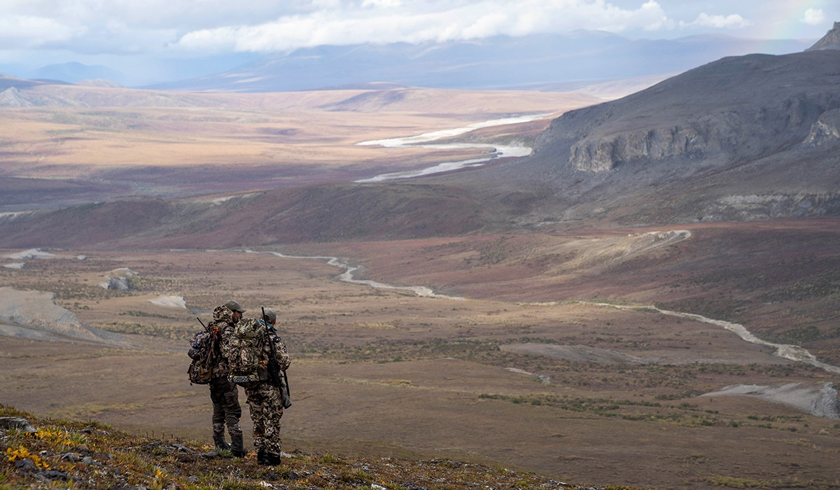 Two hunters standing on a mountain in Alaska overlooking a drainage.