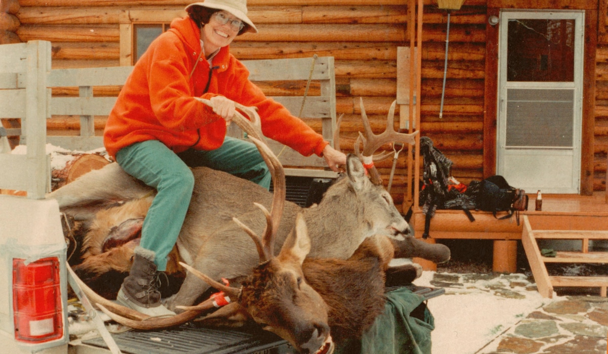 Woman hunting a bull elk and buck deer in Montana in front of a cabin.