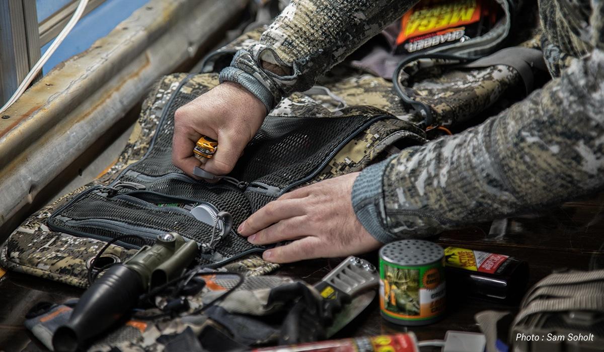 Man organizing hunting gear and calls.