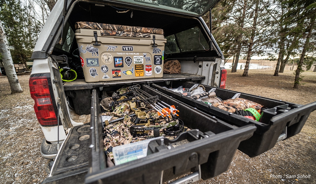 Hunter organizing the back of his truck with bow, cooler, and other gear.