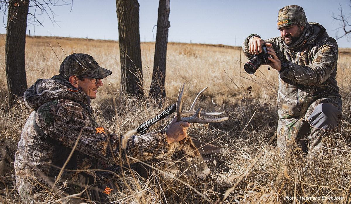Two hunters photographing a deer shot while hutning.