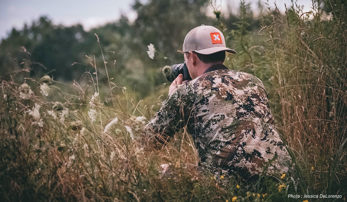 A man in camouflage with a camera in the field.