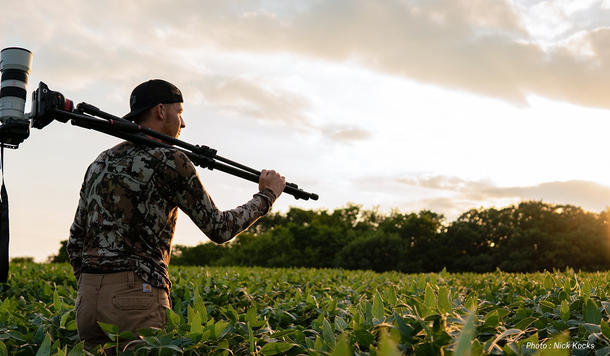 A man with camera and tripod in a planted field.