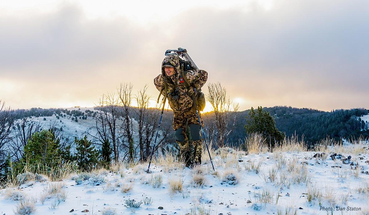 Man hunting in snow, climbing hills.