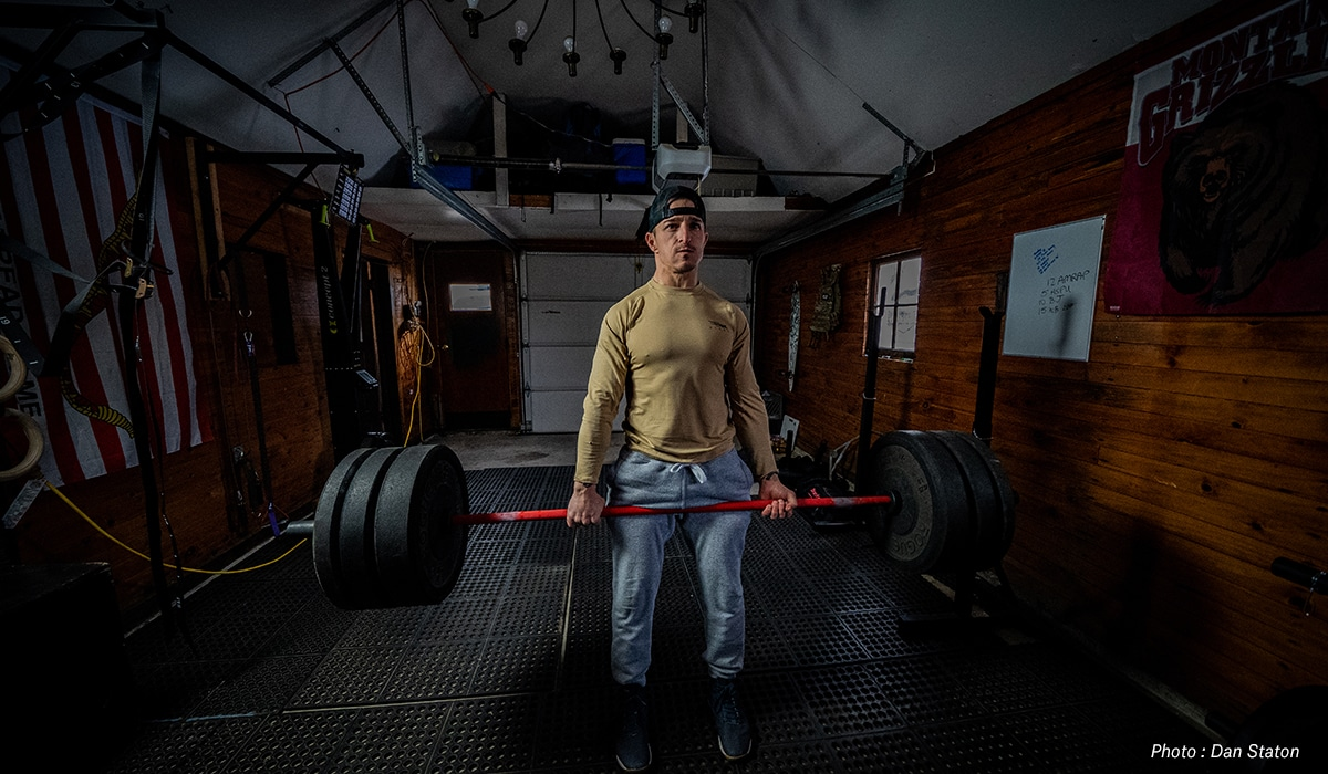 Man deadlifting in a garage, training to hunt in the mountains.