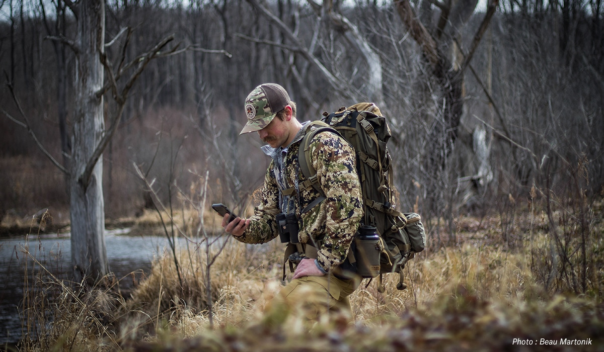 Man hunting with a pack in a wooded area, with cell phone in hand.